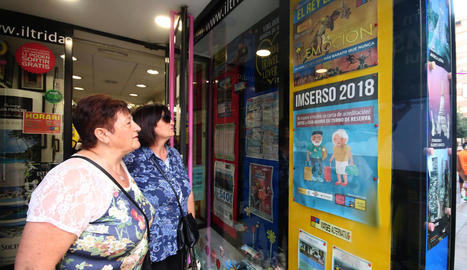 Dos dones observen el cartell de l'Imserso a l'agència d'Iltrida del carrer Sant Antoni.