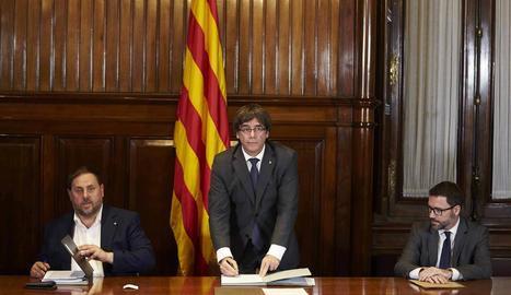 El president, Carles Puigdemont, firma la convocatòria del referèndum al costat del vicepresident, Oriol Junqueras.