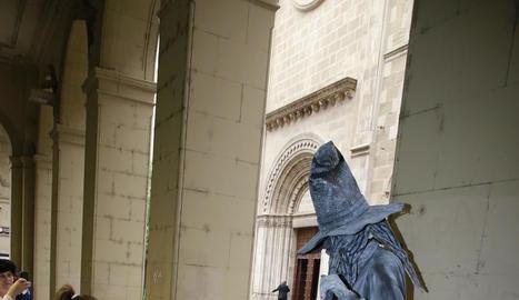 Una nena saluda una estàtua que encarnava Merlí.