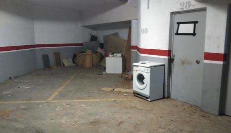 Electrodomèstics i escombraries en un racó de l'aparcament.