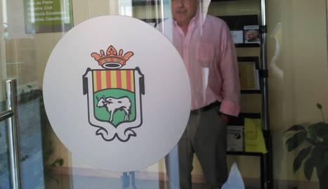 L'alcalde, Enric Mir, darrere de l'actual escut de la localitat.