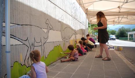Diversos nens en una de les activitats infantils, pintar un mural a l'exterior de la Dinosfera.