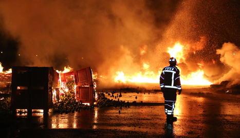 Un bomber, davant de les flames a l'exterior d'aquesta empresa situada als afores del barri de Pardinyes.