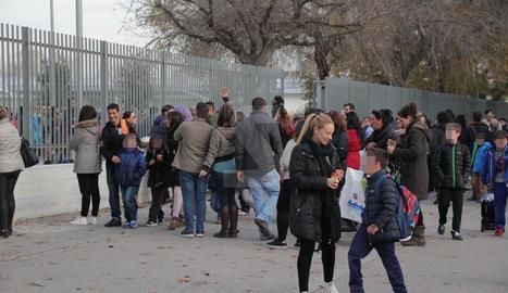 Pares i mares i alumnes a la sortida d'una escola.-