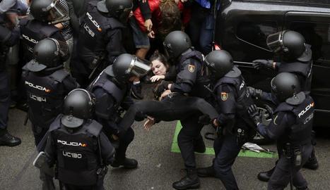 Els agents de la Policia Nacional formen un cordó policial al col·legi Ramon Llull i s'emporten una noia.