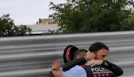 Un home consola un mosso després dels disturbis a Cappont.