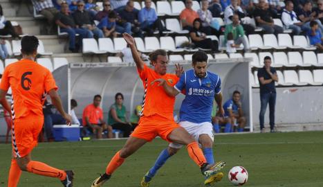 Iván Agudo, que va jugar un partit molt complet, lluita amb un jugador del Llagostera en una acció del partit d'ahir al Camp d'Esports.