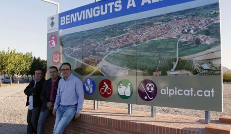 L'alcalde i dos edils, amb el cartell de benvinguda al poble.