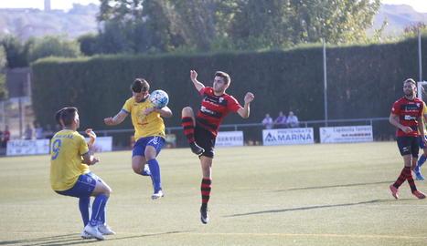 Un jugador del Vila-seca toca la pilota amb la mà davant de l'intent d'un futbolista de l'EFAC d'aconseguir el control.