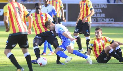 Moustapha intenta frenar l'avenç d'un jugador de l'Alcoià, amb Valiente a terra, en una acció del partit d'ahir.
