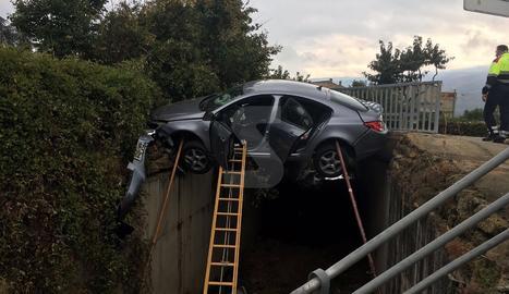 El cotxe, ja apuntalat, i l'escala amb què van rescatar el conductor