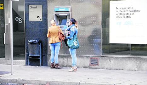 Cues de clients per treure diners en una sucursal de Caixabank, ahir a Tàrrega.