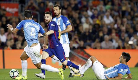 El blaugrana Sergio Busquets es llança a la gespa per prendre la pilota a l'argentí Emanuel Cecchini.
