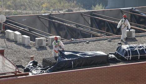 Operaris amb vestits de protecció cobreixen l'amiant retirat de la coberta de l'edifici de Mercolleida.