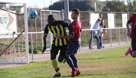 Un jugador de l'equip local intenta arribar a porteria malgrat la pressió del rival.
