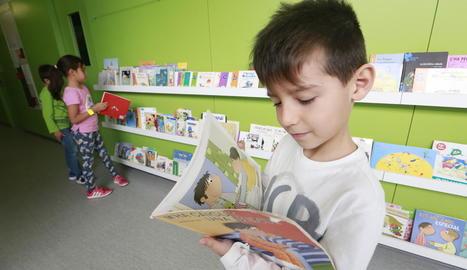 Un nen, fent una ullada a un dels llibres exposats als passadissos.