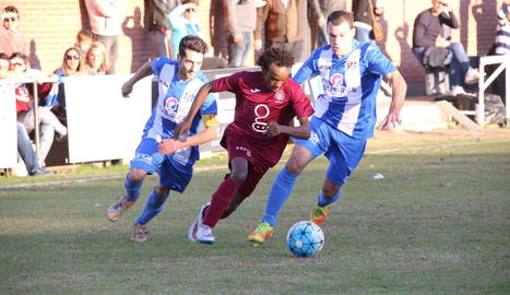 Un jugador de l'Agramunt avança amb perill davant la pressió de dos jugadors del Torregrossa.