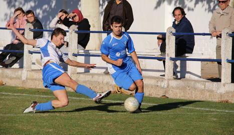Un jugador de l'equip visitant intenta prendre la pilota a un de local.
