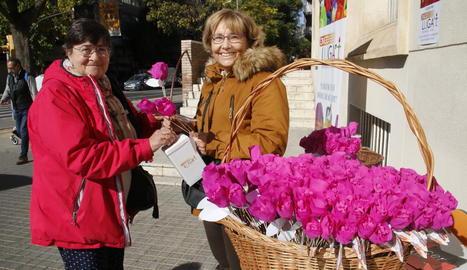 Una dona col·labora amb la iniciativa 'Una flor per a un projecte' a la taula de Ricard Viñes.