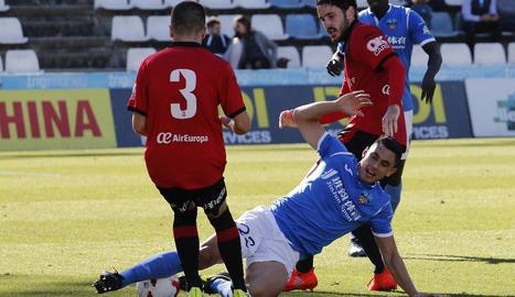 Valiente cau a terra davant de dos jugadors del Mallorca en una acció del partit d'ahir.