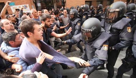 Un policia carrega contra un jove davant el col·legi de la Mariola.