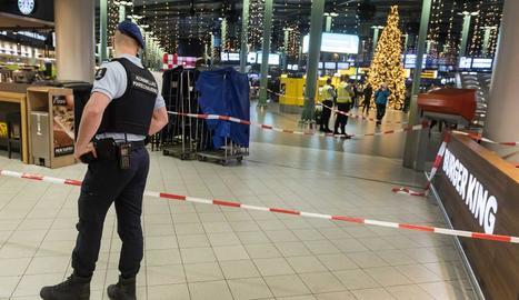 Un policia holandès controla l'interior de l'aeroport de Schiphol.