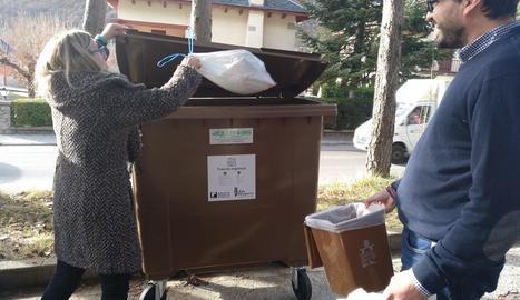 Una veïna diposita escombraries orgàniques al contenidor.
