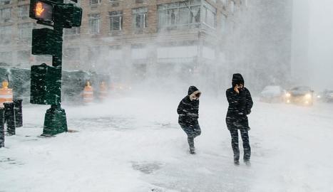 Vianants caminen en plena tempesta de neu a la ciutat de Nova York.
