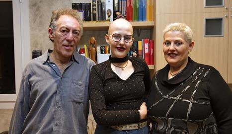 Sara, ahir, mirant un pòster de fotos en les quals apareix amb Álvaro (esquerra) i amb els seus pares, Salvador i Esther (dreta).