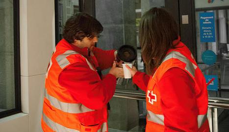 Dos voluntaris de Creu Roja Lleida serveixen cafè.