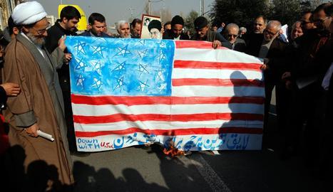 Un grup d'homes crema una bandera nord-americana durant una protesta a l'Iran.