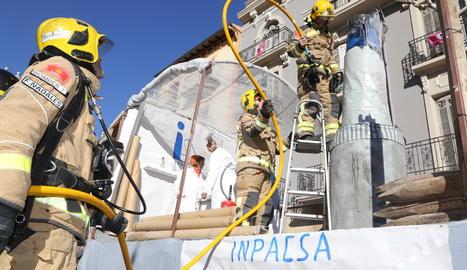 Bombers treballant en l'incendi de la decoració d'una carrossa a Balaguer.