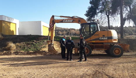 Una patrulla de la Guàrdia Urbana, amb els operaris de la màquina excavadora, al lloc de la troballa.