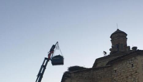 Operaris retirant nius de la teulada de l'església de Seròs.
