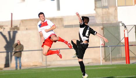 El jugador visitant Pocurull intenta avançar-se al jugador del Linyola, Alpha, que va ser l'autor del gol local que li va donar un punt a l'equip davant del Mollerussa.