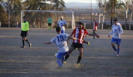 Un jugador de l'equip local i un del visitant competeixen per la pilota.