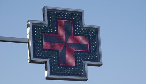 El rètol lluminós d'una farmàcia.