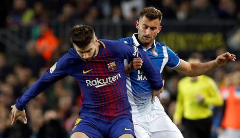 Gerard Piqué protegeix la pilota davant de Leo Baptistao.