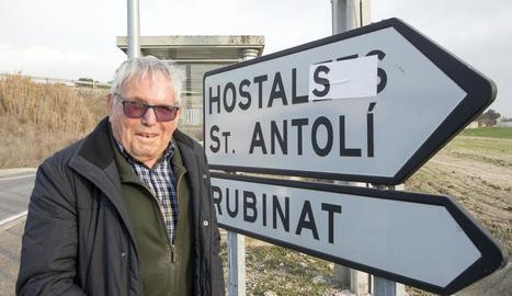 Ramon Tous, que insta l'ajuntament a canviar el nom d''Hostalets' per 'els Hostals', davant d'un senyal 'corregit' amb un adhesiu.