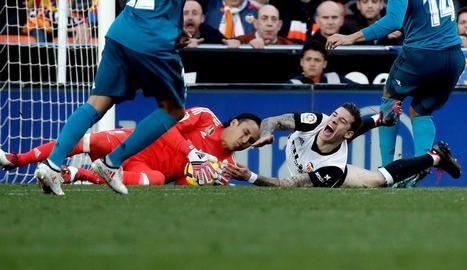 Keylor Navas agafa la pilota davant del davanter del València Santi Mina durant el partit d'ahir.
