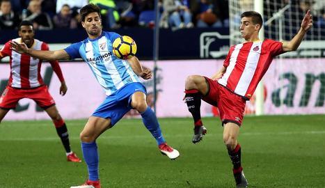 El centrecampista del Girona Pere Pons lluita una pilota amb el davanter Adrián durant el partit.