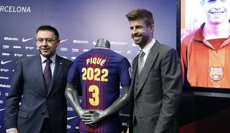 Bartomeu i Gerard Piqué flanquegen la samarreta que explicita la renovació del central fins al 2022.
