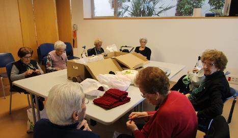 Imatge de persones grans que elaboren objectes per recaptar fons per a Creu Roja