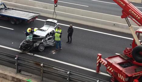 El cotxe, que es va precipitar al buit sobre l'autovia A-7, abans de ser carregat sobre la grua.