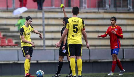 Un jugador del Balaguer passa l'esfèrica a un company davant de la pressió d'un rival.