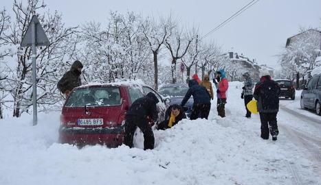 Afectats per la intensa nevada a Bellver de Cerdanya provant de col·locar cadenes als vehicles.