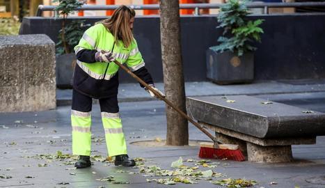 Una treballadora neteja el carrer.
