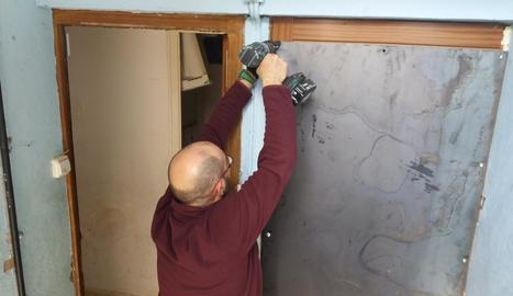 Un operari col·loca una planxa de metall en una porta d'un dels pisos desallotjats.