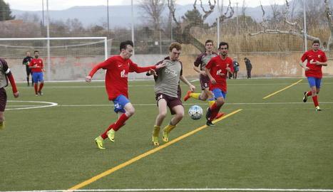 Un jugador local intenta aconseguir el control de la pilota davant la pressió d'un jugador del Bellpuig.