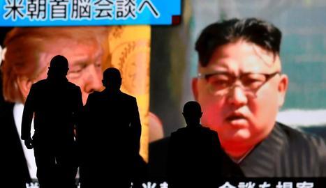 Persones passen per davant d'una pantalla amb la imatge dels líders dels EUA i Corea del Nord.